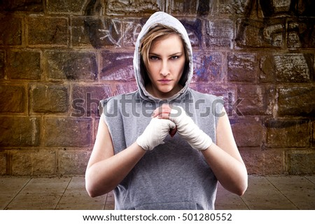 Young woman against concrete wall with graffiti