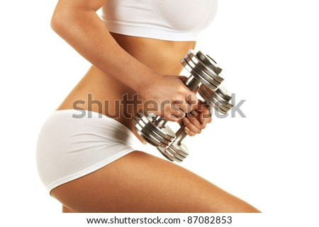 Young woman against white background with sporty body, with dumbbels - stock photo