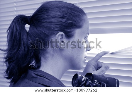 Young woman (age 25-30 ) looks and searches with binoculars and  looks out through Venetian blinds. Concept photo of curious, spy, nosy woman (BW). - stock photo