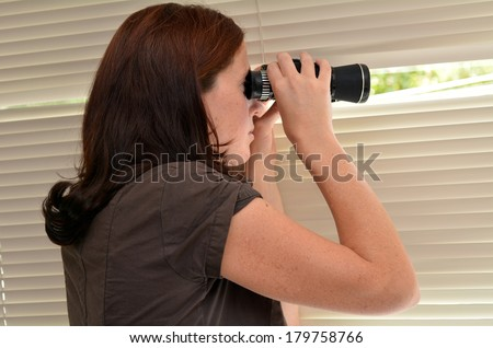 Young woman (age 25-30 ) searching with binoculars and  looks out through blinds. Concept photo of curious, spy, nosy woman - stock photo
