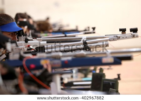 young woman aiming a pneumatic air rifle on sports competition - stock photo