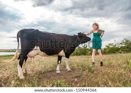 Young woman and a cow in the countryside - stock photo