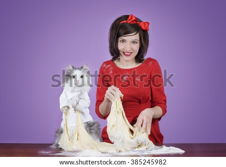 young woman and a fluffy cat preparing dough - stock photo