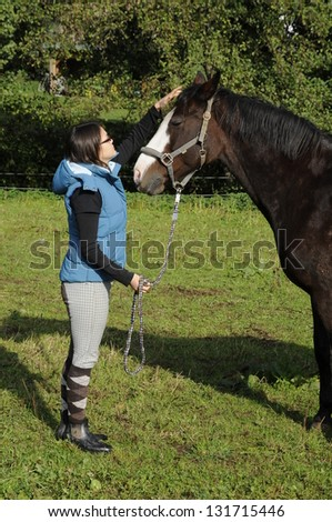 Young woman and a horse - stock photo
