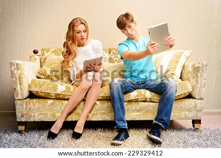 Young woman and a man sitting on a sofa and each of them looks at his own digital tablet. Relationships. Lack of of live communication. - stock photo