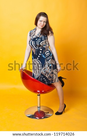 young woman and a red chair - stock photo