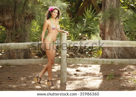 Young woman and a wooden farm fence
