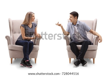 Young woman and a young man sitting in armchairs and talking isolated on white background