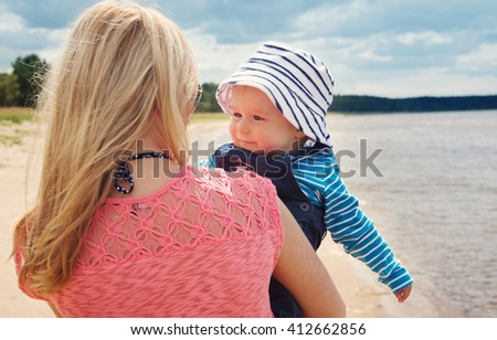 young woman and baby at the beach near sea - stock photo