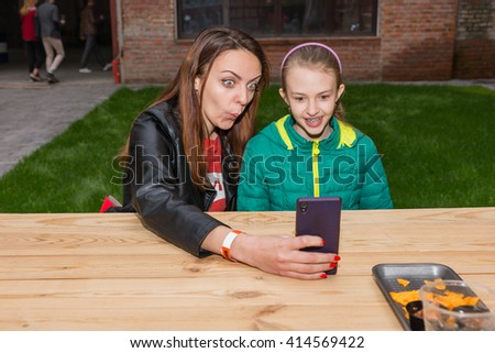 Young Woman and Brunette Girl Making Funny Facial Expressions and Taking Selfie Self Portraits with Cell Phone While Seated at Picnic Table Outdoors - stock photo