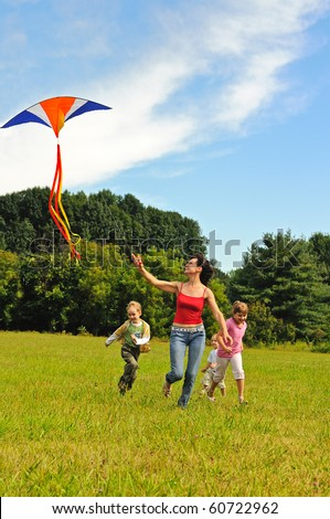 Young woman and children flying a kite - stock photo