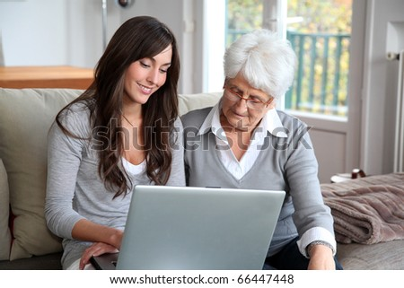 Young woman and elderly woman with laptop computer - stock photo