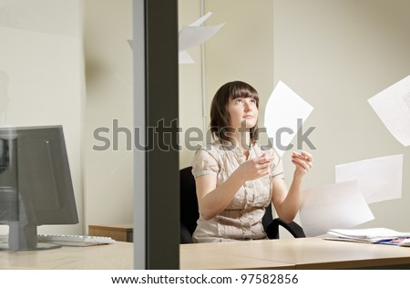 Young woman and flying papers in office - stock photo