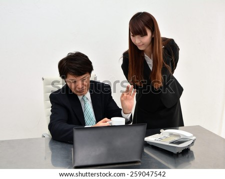 Young woman and her boss watching at laptop screen