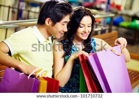 Young woman and her boyfriend looking in the shopping bag with sweet anticipation - stock photo