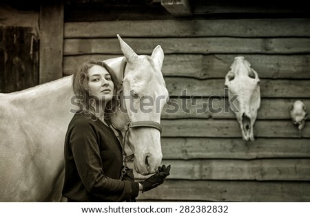 Young woman and her cremello horse on the background of horse and deer skulls - stock photo