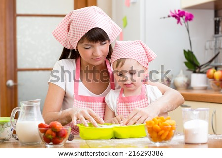Young woman and her daughter making berry fruit cake - stock photo