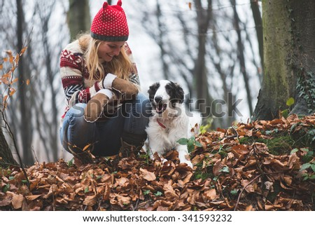 Young woman and her dog posing outdoor in the forest