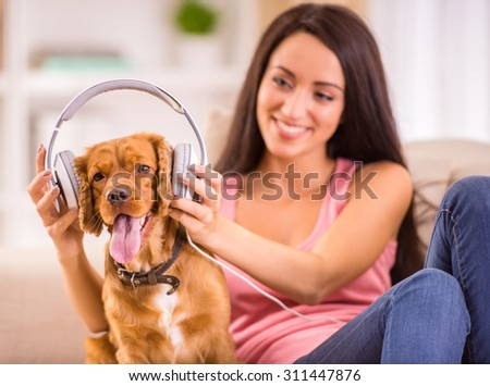 Young woman and her dog with headphone is listening a music. - stock photo