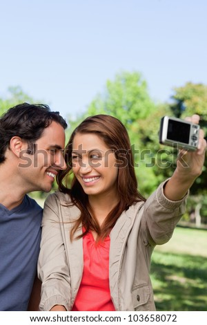 Young woman and her friend look at each other while she takes a photo of them together using her camera - stock photo