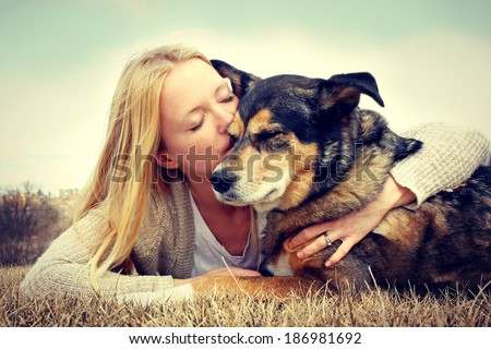 Young woman and her German Shepherd dog lying in the grass, she is hugging and kissing him. Vintage style color. - stock photo
