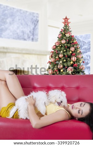Young woman and her puppy sleeping on the sofa at home, shot with a christmas tree background - stock photo