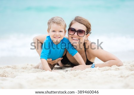 Young woman and her son having fun on the beach - stock photo