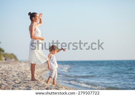 Young woman and her son standing by the sea looking at sunset