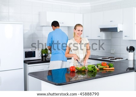 young woman and husband preparing food in kitchen