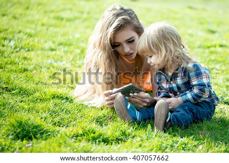 young woman and little boy with mobile phone lying in the field on green grass sunny day