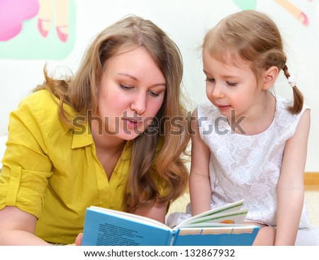 Young woman and little girl read a book - stock photo