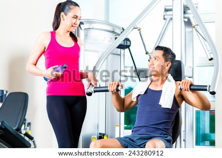 Young woman and man chatting at gym