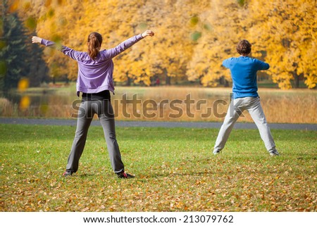 Young woman and man doing physical exercises outdoors