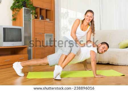 Young  woman and man doing regular exercises together at home