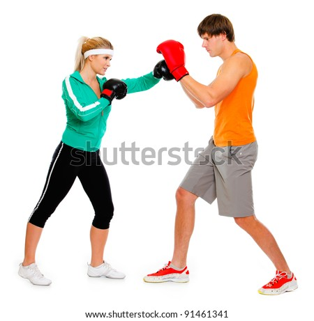 Young woman and man in boxing gloves practicing isolated on white