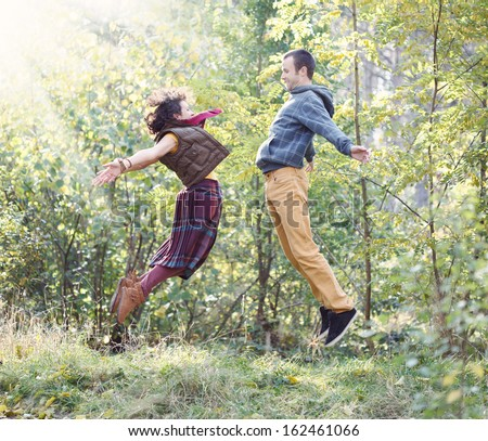 Young woman and man in bright clothes jumping to meet each other in the park - stock photo