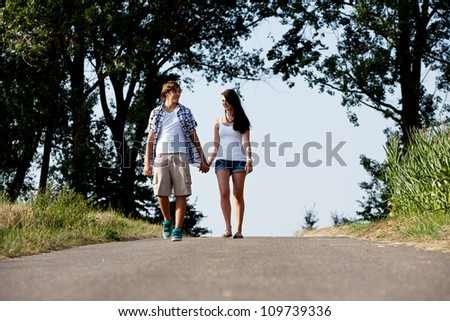 young woman and man is walking on  a road in summer outdoor happy