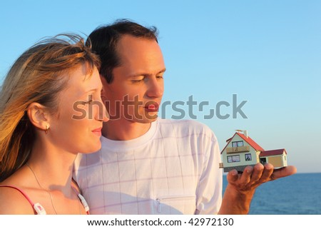 Young woman and man keeping in hands model of house with garage against sea in summer - stock photo