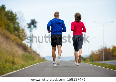 Young woman and man running in park
