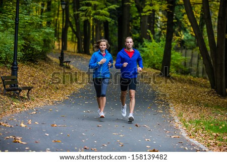Young woman and man running in park - stock photo