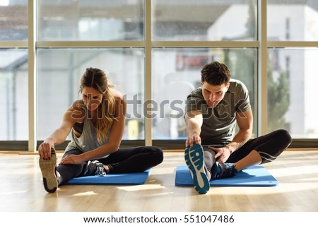 Young woman and man working out indoors. Two people stretching their legs on the floor of a gym.