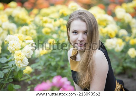 Young woman  and many yellow roses around her - stock photo