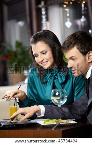 Young woman and the man discuss something on the laptop screen in cafe - stock photo