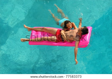 Young woman and the man on a mattress in pool - stock photo