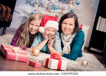 Young woman and two her daughters getting Christmas gifts - stock photo