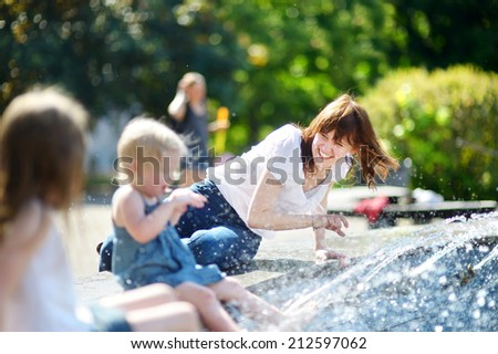 Young woman and two little kids having fun by a city fountain on hot and sunny summer day - stock photo