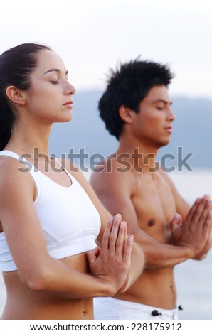 Young woman and young man with hands folded outdoors - stock photo