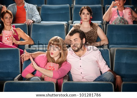 Young woman annoyed with boyfriend in theater - stock photo