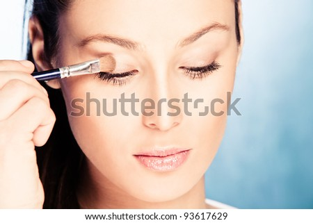 young woman apply eyeshadow with cosmetic brush, looking down,  studio shot - stock photo