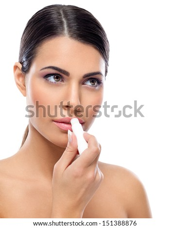 Young woman applying balsam on lips - stock photo